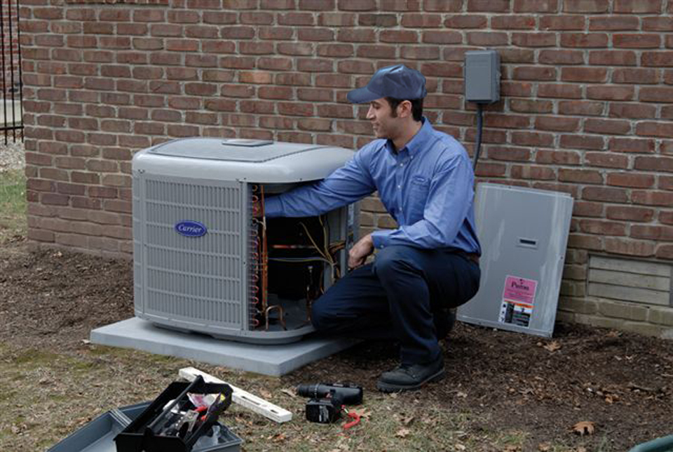 AC repair tech examines system