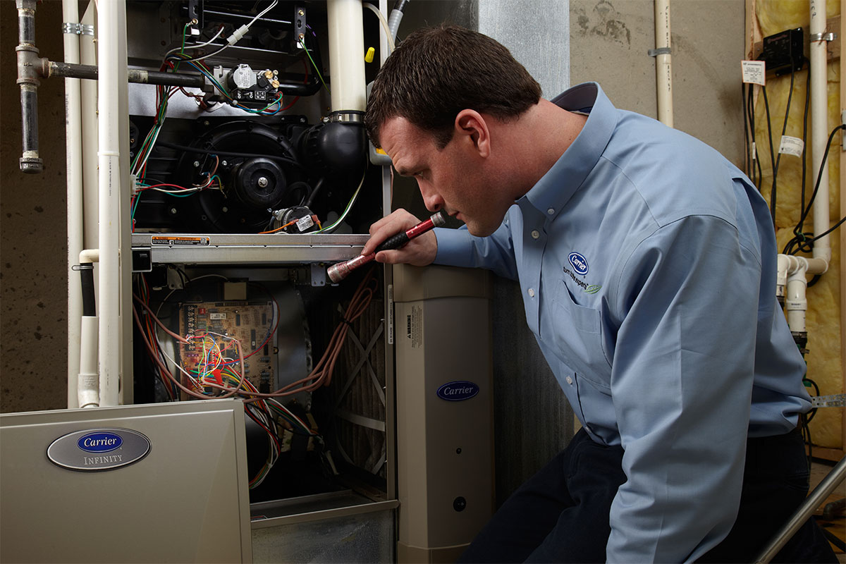 Furnace repair tech examines HVAC system