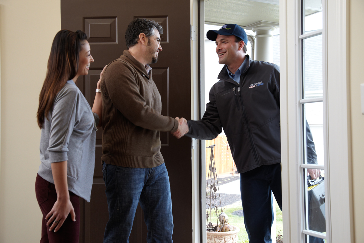 Customers and HVAC installer meet at door
